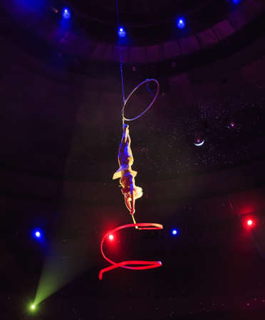 Aerial acrobat in the ring. A young girl performs the acrobatic elements with tape in the air ring