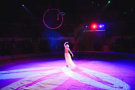 Aerial acrobat in the ring. A young girl performs the acrobatic elements in the air ring 写真素材 - 131694098