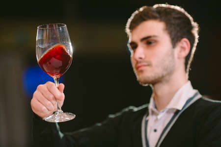 This wine is just perfect. Confident male sommelier examining glass with wine