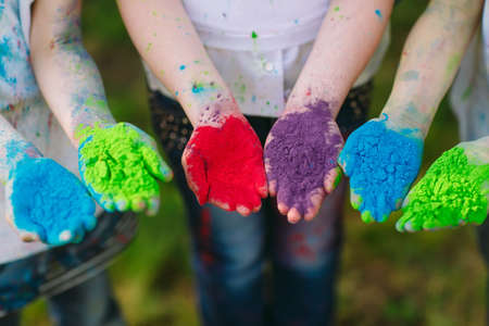 Hands Palms of young people covered in purple, yellow, red, blue Holi festival colors isolated.