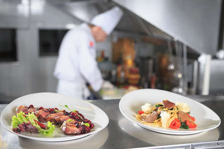 the distribution table in the kitchen of the restaurant. the chef prepares a meal on the background of the finished dishes. Imagens