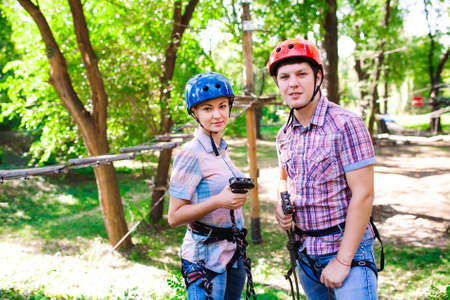 adventure climbing high wire park - people on course in mountain helmet and safety equipment 写真素材 - 131693622