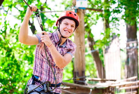 adventure climbing high wire park - people on course in mountain helmet and safety equipment 写真素材 - 131694065
