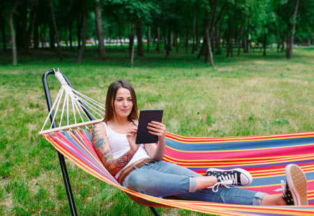 Young woman with tablet on the hammock.