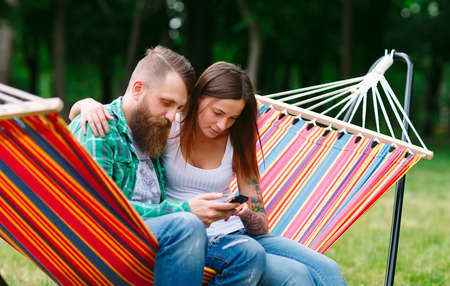 Young couple with mobile phone sitting on hammock.