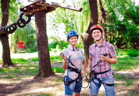 adventure climbing high wire park - people on course in mountain helmet and safety equipment 写真素材 - 131693695