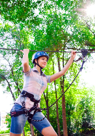 adventure climbing high wire park - people on course in mountain helmet and safety equipment 写真素材