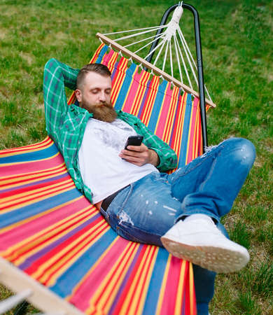 man using an app on his mobile phone white swinging in a hammock.
