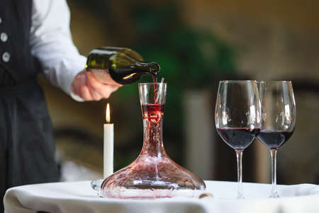 A sommelier pouring red wine into decanter. Stock Photo