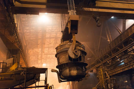Melting of metal in a steel plant. High temperature in the melting furnace. Metallurgical industry. Factory for the manufacture of metal pipes. Bucket for feeding metal into molds. Banco de Imagens