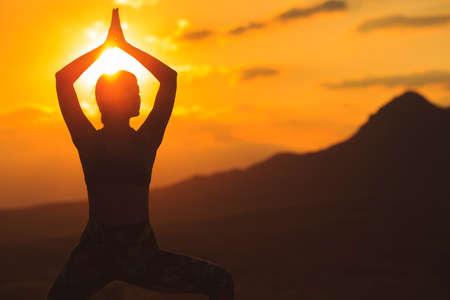 Silhouette de jeune femme pratiquant le yoga ou le pilates au coucher du soleil ou au lever du soleil dans un bel endroit de montagne