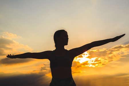 Silhouette di giovane donna che pratica yoga o pilates al tramonto o all'alba in una splendida località di montagna, facendo esercizi di affondo, in piedi in Warrior