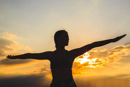 Silhouette of young woman practicing yoga or pilates at sunset or sunrise in beautiful mountain location, doing lunge exercise, standing in Warrior