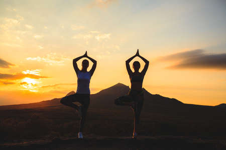 Silhouette of young womans practicing yoga or pilates at sunset or sunrise in beautiful mountain location. Banque d'images