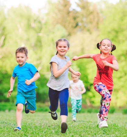 Molti bambini, ragazzi e ragazze diversi che corrono nel parco durante la soleggiata giornata estiva in abiti casual. Archivio Fotografico