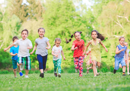 Many different kids, boys and girls running in the park on sunny summer day in casual clothes. Stock Photo