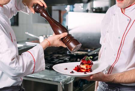Two Chefs Sha background kitchen pepper dishes.