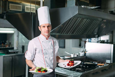 Portrait of the Chef in the kitchen of the restaurant with a ready-made dish Foie Gras.