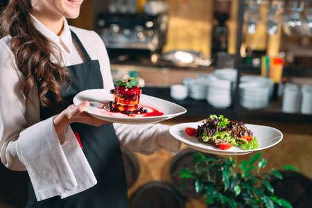 Ober in beweging in dienst in restaurant. De ober draagt gerechten.