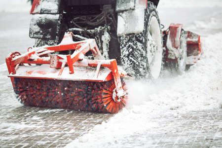 City service cleaning snow , a small tractor with a rotating brush clears a road in the city park from the fresh fallen snow on winter day