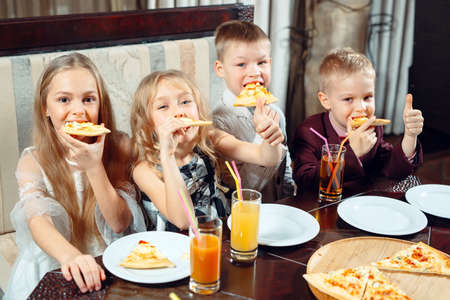 company of children eat pizza in the restaurant