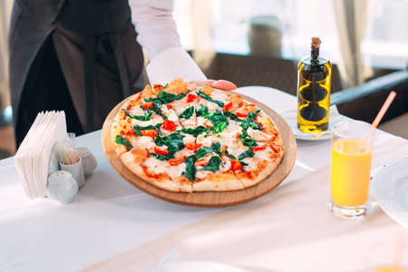 The waiter puts pizza On the table in the Restaurant.
