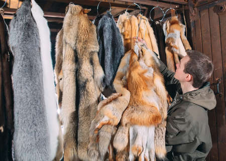 A young man hangs up the fur after treatment.