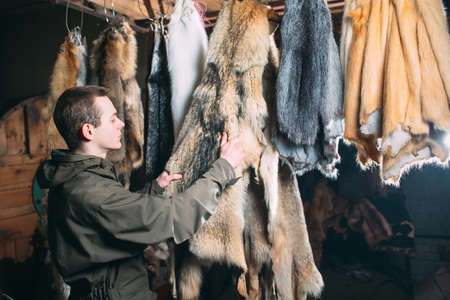 A young man hangs up the fur after treatment Banque d'images