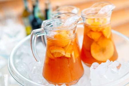 Jugs of fruit lemonade in the ice.