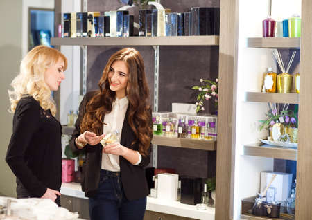 Polite female consultant helping customer with choice in cosmetics store.