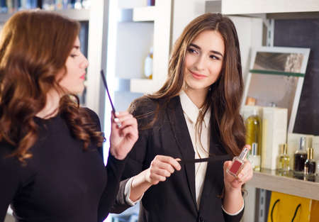 Polite female consultant helping customer with choice in cosmetics store. Stock Photo