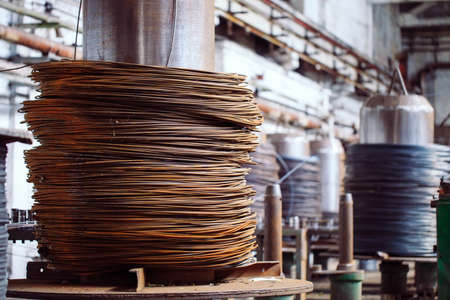 Wire rod, fittings in warehouses. industrial storehouse at the metallurgical plant Archivio Fotografico - 128252563