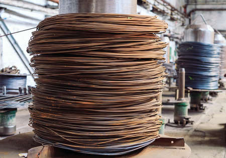 Wire rod, fittings in warehouses. industrial storehouse at the metallurgical plant. Archivio Fotografico - 128252733