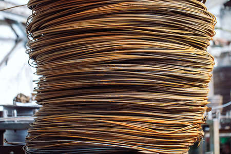 Wire rod, fittings in warehouses. industrial storehouse at the metallurgical plant. Archivio Fotografico - 128252746