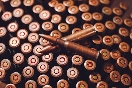 Bullets on a wooden background. Military concept.