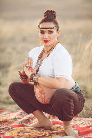 Pregnant woman doing yoga in the field at sunset
