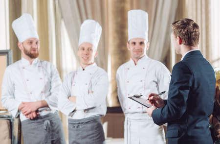 direttore del ristorante e il suo staff in cucina. interagire con il capo chef in una cucina commerciale