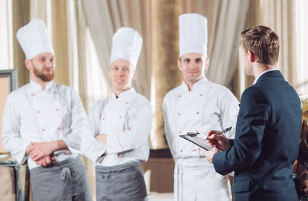 restaurant manager and his staff in kitchen. interacting to head chef in commercial kitchen Banco de Imagens