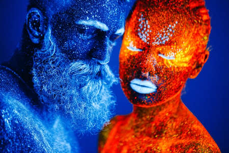 Concept. Portrait of a bearded man and woman painted in ultraviolet powder