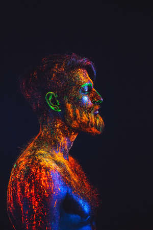 Concept. Portrait of a bearded man. The man is painted in ultraviolet powder