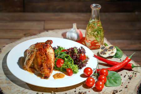 Fried chicken with vegetables on a white plate on the background of a wooden table