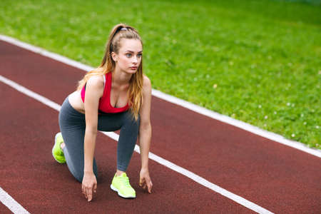 Beautiful athlete on a race track is ready to run.