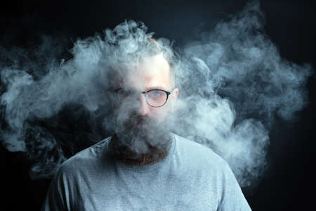 Concept. Smoke enveloped the head man. Portrait of a Bearded, stylish man with smoke. Secondhand smoke.
