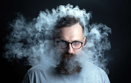 Concept. Smoke enveloped the head man. Portrait of a Bearded, stylish man with smoke. Secondhand smoke