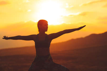 Silueta de mujer joven practicando yoga o pilates al atardecer o al amanecer en una hermosa ubicación de montaña. Foto de archivo