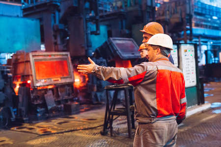 Workers in the steel mill. Factory worker takes a sample for metal.