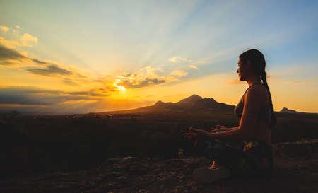 Junge Frau, die Yoga oder Pilates bei Sonnenuntergang oder Sonnenaufgang in schöner Berglage praktiziert. Standard-Bild