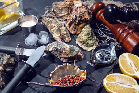 Oysters on stone plate with ice, lemon, fishing net, pepper and knife