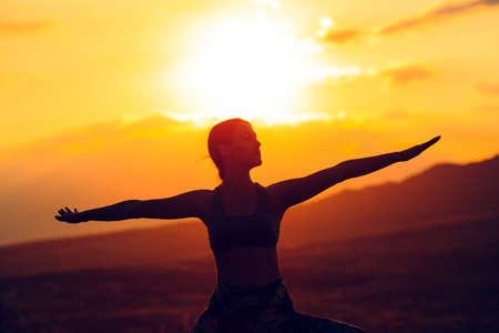 Silhouette der jungen Frau, die Yoga oder Pilates bei Sonnenuntergang oder Sonnenaufgang in schöner Berglage praktiziert.