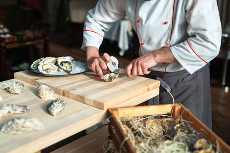 Opening the hollow and flat oysters. Chef opens oysters in the restaurant.